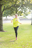 Active smiling blonde jogging towards camera