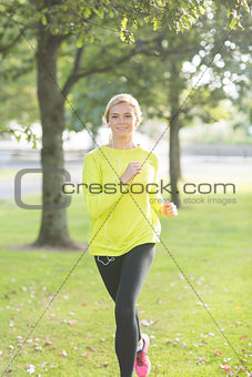 Active happy blonde jogging towards camera