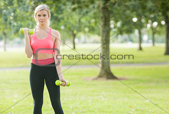 Active attractive blonde lifting dumbbells