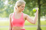 Active smiling blonde lifting dumbbells