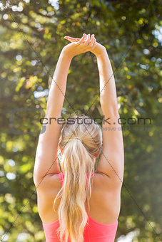 Active blonde stretching her arms