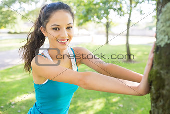 Active cheerful brunette stretching her leg