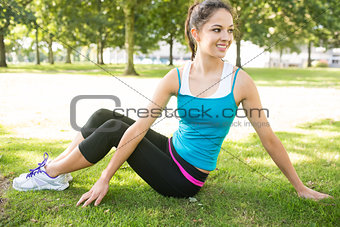 Active smiling brunette stretching her back