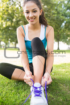 Active smiling brunette tying her shoelaces