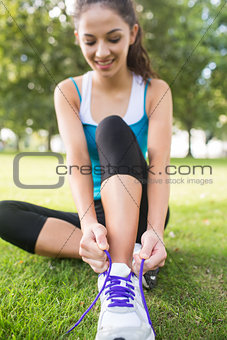Active happy brunette tying her shoelaces