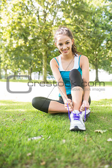 Smiling active brunette tying her shoelaces