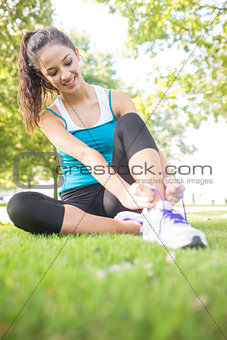 Happy active brunette tying her shoelaces