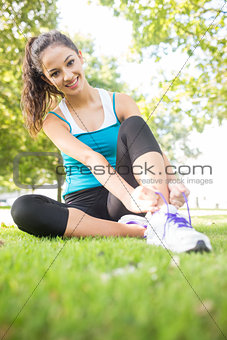 Cheerful active brunette tying her shoelaces