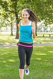 Active smiling brunette jogging