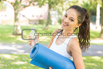 Active smiling brunette holding exercise mat