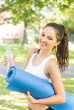 Active cheerful brunette holding exercise mat