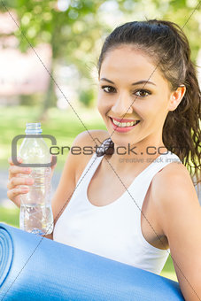 Active happy brunette holding exercise mat