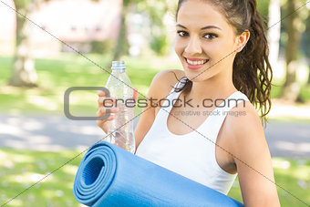 Active content brunette holding exercise mat