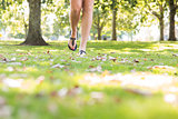 Close up of female feet wearing sandals walking on grass