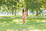 Stylish happy brunette walking on grass