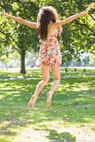 Rear view of beautiful stylish brunette jumping in the air