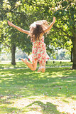Rear view of attractive stylish brunette jumping in the air