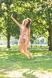 Stylish cheerful brunette jumping in the air