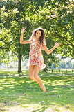 Stylish happy brunette jumping in the air