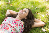 Stylish cheerful brunette lying on the grass