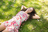 Stylish smiling brunette lying on the grass