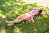 Stylish happy brunette lying on the grass