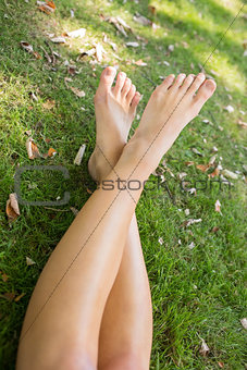 Close up of a womans crossed legs lying on the grass