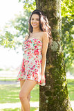Stylish gorgeous brunette leaning against tree