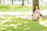 Stylish cheerful brunette sitting and leaning against tree