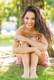 Stylish smiling brunette sitting under a tree