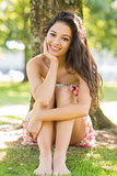 Stylish happy brunette sitting under a tree