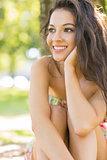Stylish attractive brunette sitting under a tree