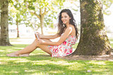Stylish smiling brunette sitting under a tree using tablet