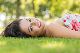 Stylish smiling brunette lying on a lawn