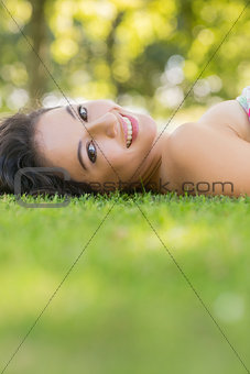 Stylish cheerful brunette lying on a lawn
