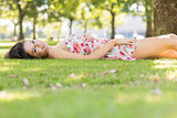 Stylish happy brunette lying on a lawn