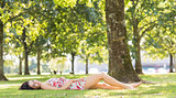 Stylish pretty brunette lying on a lawn