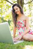 Stylish cheerful brunette sitting on a lawn using laptop