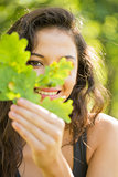 Gorgeous smiling brunette holding a leaf