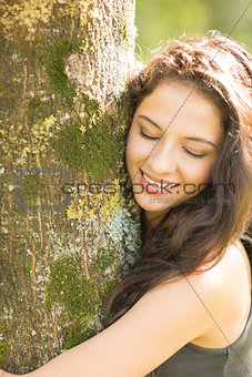 Casual smiling brunette embracing a tree with closed eyes