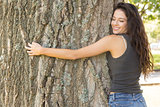 Casual attractive brunette embracing a tree with closed eyes