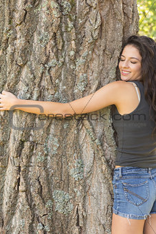 Casual beautiful brunette embracing a tree with closed eyes
