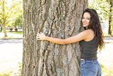 Casual gorgeous brunette embracing a tree looking at camera