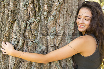 Casual gorgeous brunette embracing a tree with closed eyes