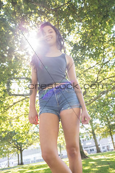 Casual gorgeous brunette standing on grass in sunlight