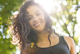 Casual smiling brunette standing on grass in sunlight