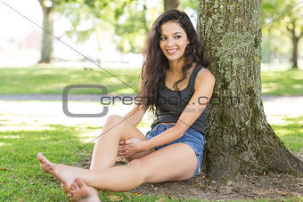 Casual happy brunette sitting leaning against tree