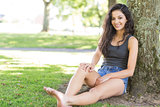 Casual attractive brunette sitting leaning against tree