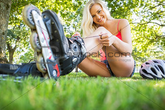 Casual happy blonde tying shoelaces of roller blades
