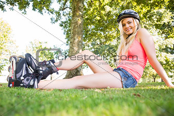 Casual smiling blonde wearing roller blades and helmet
